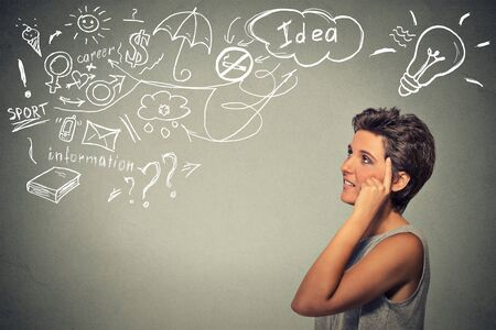 feeling happy: Portrait happy young woman thinking dreaming has many ideas looking up isolated grey wall background. Positive human face expression emotion feeling life perception. Decision making process concept