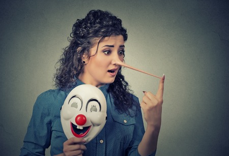 long nose: Woman with long nose and clown mask isolated on grey wall background. Liar concept. Human face expressions, emotions, feelings.