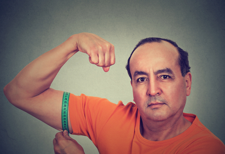 fitness goal: Closeup middle aged man flexing his muscle measuring his biceps isolated on gray wall background. Fitness goal achievement result concept