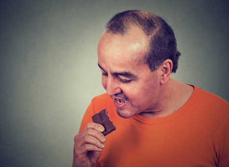 obsession: Portrait middle aged man tired of diet restrictions craving sweets chocolate isolated on gray wall background. Human face expression emotion. Nutrition concept. Feelings of guilt. Funny looking guy