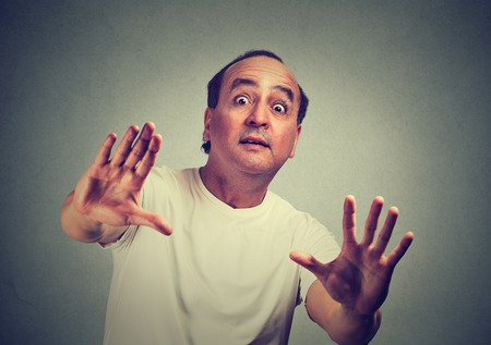 avoid: Middle aged handsome man scared with shocked facial expression trying to protect himself from unpleasant situation object thrown at him isolated gray background. Negative emotion feeling reaction Stock Photo