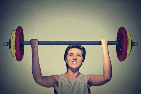 woman work: Strong woman lifting heavy barbell isolated on gray wall background. Determination task completion hard work concept Stock Photo