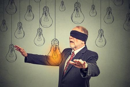 ojos vendados: Hombre mayor con los ojos vendados caminando a trav�s de las bombillas en busca de brillante idea aislada en el fondo de la pared gris