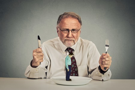 dissect: Serious elderly business man with knife and fork ready for deal negotiation new proposal looking at his employee on a plate isolated on gray wall background