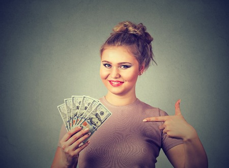 financial reward: Closeup portrait super happy excited successful young business woman holding money dollar bills in hand isolated gray wall background. Positive emotion facial expression feeling. Financial reward