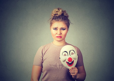 Portrait young upset worried woman with sad expression holding a clown mask expressing cheerfulness happiness isolated on gray wall background. Human emotions Foto de archivo