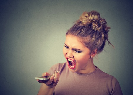 cranky: Portrait angry young woman screaming on mobile phone isolated on gray wall background. Negative human emotions feelings