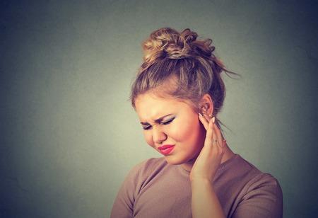 dolor de oido: Tinnitus. perfil lateral del primer mujer joven enferma que tiene dolor de oído tocar su dolor de cabeza aislado en el fondo de la pared gris Foto de archivo