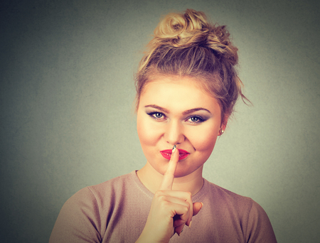 noiseless: Closeup portrait of beautiful young woman with finger on lips isolated on gray wall background. Human body language signs symbols Stock Photo
