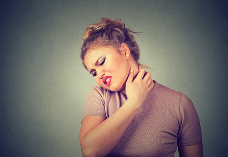 woman muscle: Back and spine disease. Closeup portrait tired woman massaging her painful neck isolated on gray wall background. Human face expression. Chronic fatigue disease Stock Photo