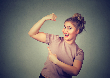 chubby girl: Closeup portrait young happy woman flexing muscles showing her strength isolated on grey wall background. Positive emotion facial expression feeling attitude perception wellbeing. Weight loss concept Stock Photo