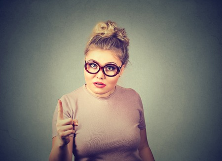 chubby: Portrait of an angry woman with finger pointing up looking displeased isolated on gray wall background. Negative human emotion feeling face expression