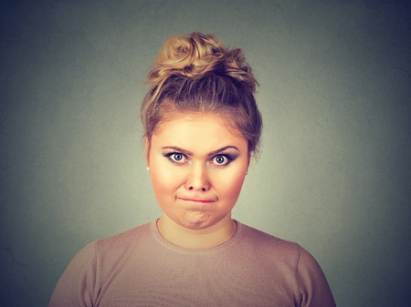 aggravated: Closeup portrait angry young pissed off woman about to have nervous breakdown isolated on gray wall background. Negative human emotions facial expression feelings attitude Stock Photo