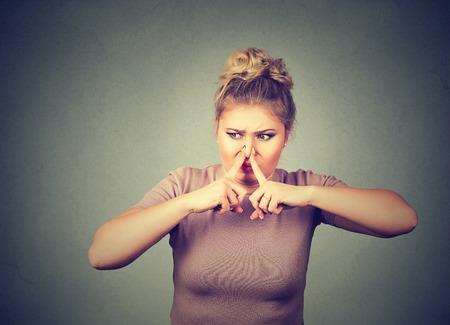olfato: mujer Retrato del primer pellizca la nariz con los dedos de las manos se ve con disgusto algo huele mal olor situación aislada en el fondo de la pared gris. reacción lenguaje corporal expresión de la cara humana Foto de archivo