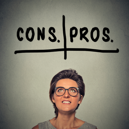 pros: pros and cons, for and against argument concept. Young business woman with glasses looking up deciding isolated on gray wall background. Face expression, emotion, feeling, perception, vision, decision