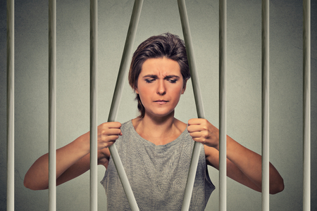 behind: Stressed desperate sad woman bending bars of her prison cell isolated on grey wall background. Life limitations, law violation consequences concept. Face expression emotion