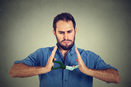 Conceptual creative shot of a man between hands of an angry guy isolated on gray wall background Stock Photo
