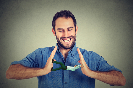Conceptual creative shot of a man between hands of a laughing smiling guy isolated on gray wall background