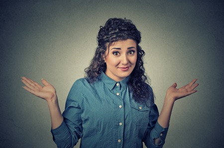 Portrait dumb looking woman arms out shrugs shoulders who cares so what I dont know isolated on gray wall background. Negative human emotion, facial expression body language life perception attitude Stock Photo