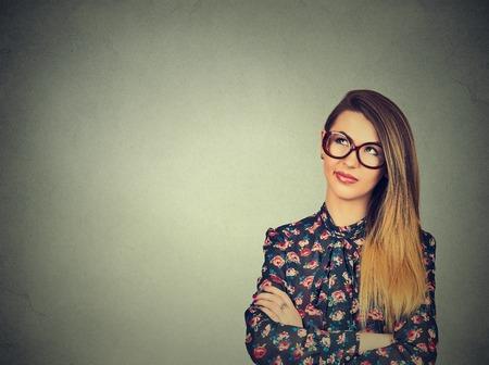 mente humana: Retrato de detalle divertido confundirse mujer joven escéptico en vasos de pensar mirando hacia arriba aislados en el fondo gris de la pared copia espacio por encima de la cabeza. expresiones humanas, las emociones, los sentimientos, el lenguaje corporal