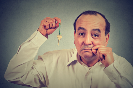shushing: Man with mouth shut holding a key isolated on gray wall background