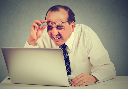 business problems: Closeup portrait middle aged business man with glasses having eyesight problems confused with laptop software isolated on gray background. Age related changes. Human face expression