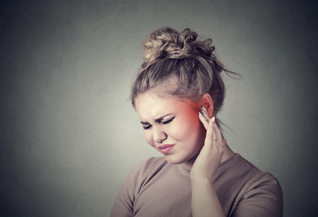 neuralgia: Tinnitus. Closeup up side profile sick female having ear pain touching her painful head colored in red isolated on gray background