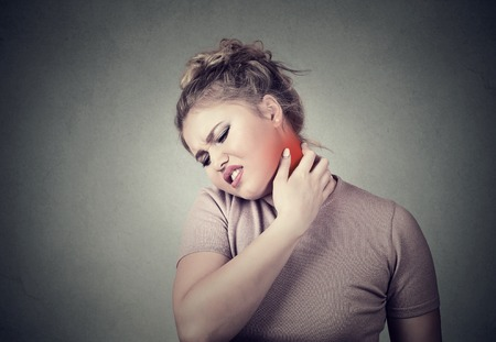 muscle spasm: Neck pain. Closeup portrait tired young woman massaging her painful neck colored in red isolated on gray wall background. Human face expression. Chronic fatigue disease Stock Photo