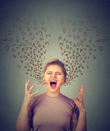 languages: portrait angry woman screaming, alphabet letters coming out of open mouth, isolated gray wall background. Negative human face expressions, emotion, reaction. Conflict, confrontation concept
