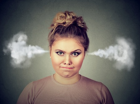 Closeup portrait of angry young woman, blowing steam coming out of ears, about to have nervous atomic breakdown isolated on black background. Negative human emotion facial expression feelings attitude Stock Photo