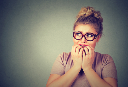 socially: Closeup portrait nervous stressed young nerdy woman in glasses biting fingernails looking anxiously craving something isolated gray background. Human emotion face expression feeling reaction Stock Photo