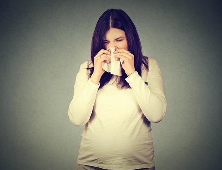 inmunidad: embarazada estornudos mujer que tiene frío que sopla la nariz que moquea aislado en el fondo de la pared gris Foto de archivo