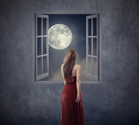 Beautiful woman in red dress walking to opened window with moon. Elements of this image furnished by NASA