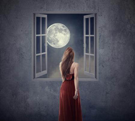noche y luna: hermosa mujer de vestido rojo caminar a la ventana abierta con la luna. Los elementos de esta imagen proporcionada por la NASA