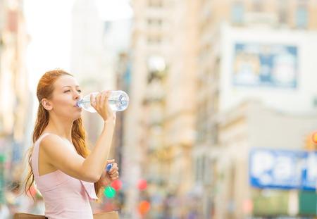 sediento: mujer joven sed. Mujer de agua potable de la botella de pl�stico en una ciudad en un d�a caluroso de verano Foto de archivo