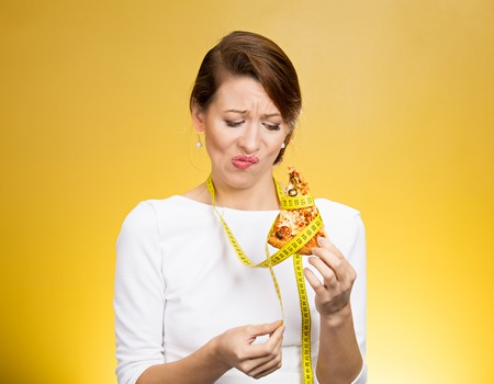 craving: Closeup portrait sad, young, confused woman holding, looking at fatty pizza with measuring tape around craving junk food trying to resist temptation to eat isolated yellow background. Face expression