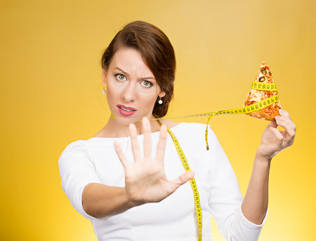 bad diet: Closeup portrait serious woman saying no to fatty pizza with measuring tape around, trying to withstand, resist temptation to eat it isolated on yellow background. Human facial expression