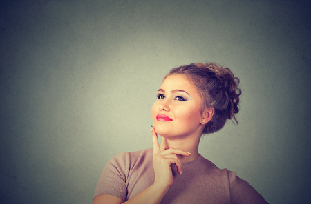 Portrait side profile happy beautiful woman thinking looking up isolated on grey wall background with copy space. Human face expressions, emotions, feelings, body language, perception Stock Photo