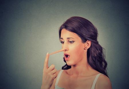 Donna con il naso lungo isolato su sfondo grigio muro. Concetto bugiardo. Espressioni umane viso, emozioni, sentimenti.