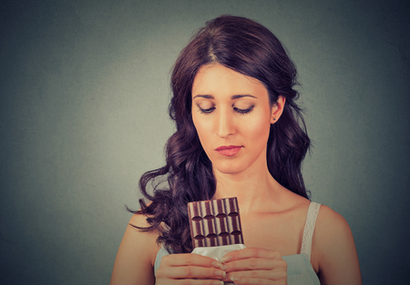delight: Portrait sad young woman tired of diet restrictions craving sweets chocolate isolated on gray wall background. Human face expression emotion. Nutrition concept. Feelings of guilt