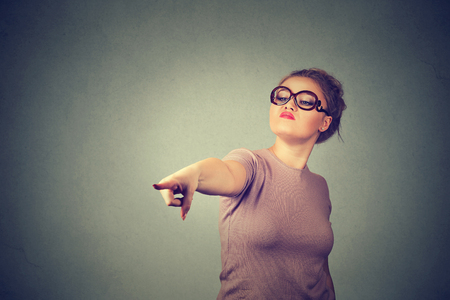bitchy: angry young woman pointing finger at camera isolated on gray wall background. Negative human emotions feelings face expression Stock Photo
