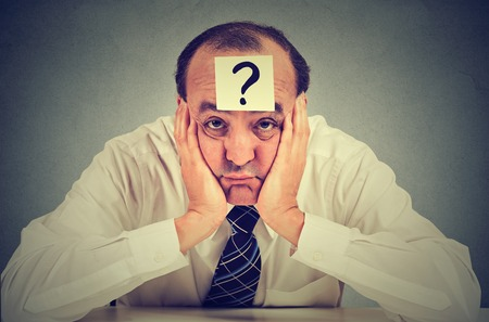 clueless business man with question mark sitting at table isolated on gray wall background Stock Photo