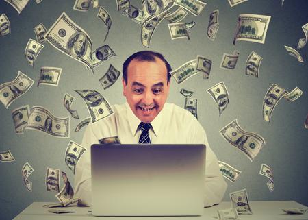 Mittlerer gealterter Geschäftsmann, der einen Laptop bauen Online-Geschäft Geld-Dollar-Scheine Bargeld unten fallen werden. Geld regen Anfänger IT Unternehmer Erfolg Economy-Konzept