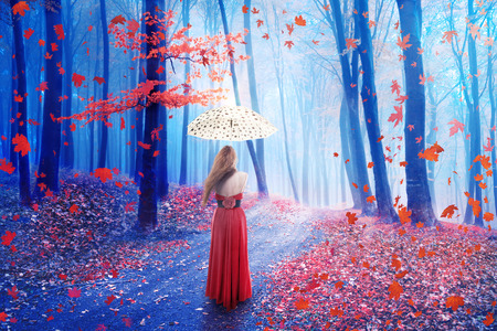 realm: Fantasy image of a beautiful lonely young woman with umbrella walking in a forest in fairy and dreamy realm. Nature background