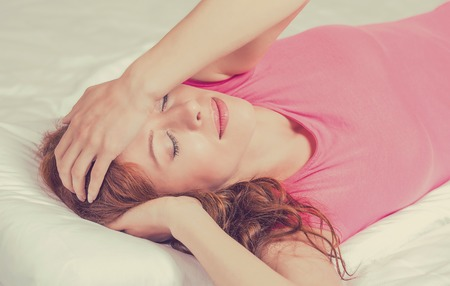 Sad young woman lying in bed with her arms on head and eyes closed having headache stressed. Human face expression emotion Stock Photo