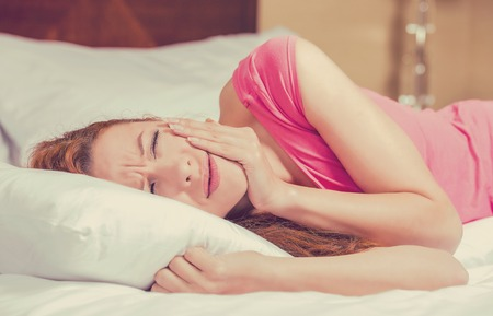 amalgam: Young woman with toothache lying in the bed. Negative human emotion face expression feeling