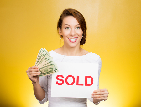 auction win: Closeup portrait happy excited successful young business woman holding red sold sign and cash dollar bills isolated yellow background. Positive emotion feeling. Financial reward Stock Photo