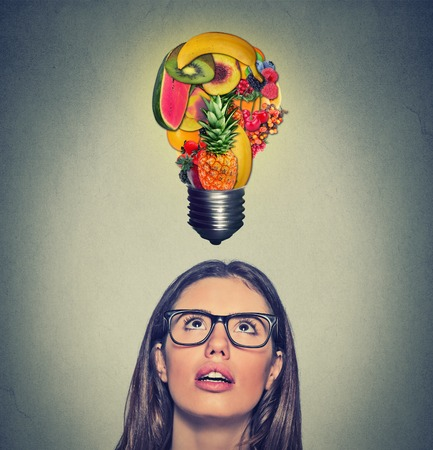 healthy looking: Eating healthy idea and diet tips concept. Closeup portrait headshot woman looking up light bulb made of fruits above head on gray wall background.