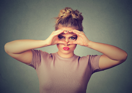 displeased: Displeased upset young woman looking through fingers like binoculars isolated on gray wall background Stock Photo
