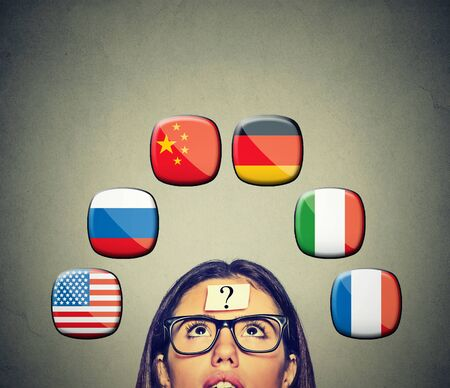 foreign country: Work and travel immigration opportunity concept. Foreign language studying process. Woman with question mark and many icons of international flags above head isolated on gray wall background.